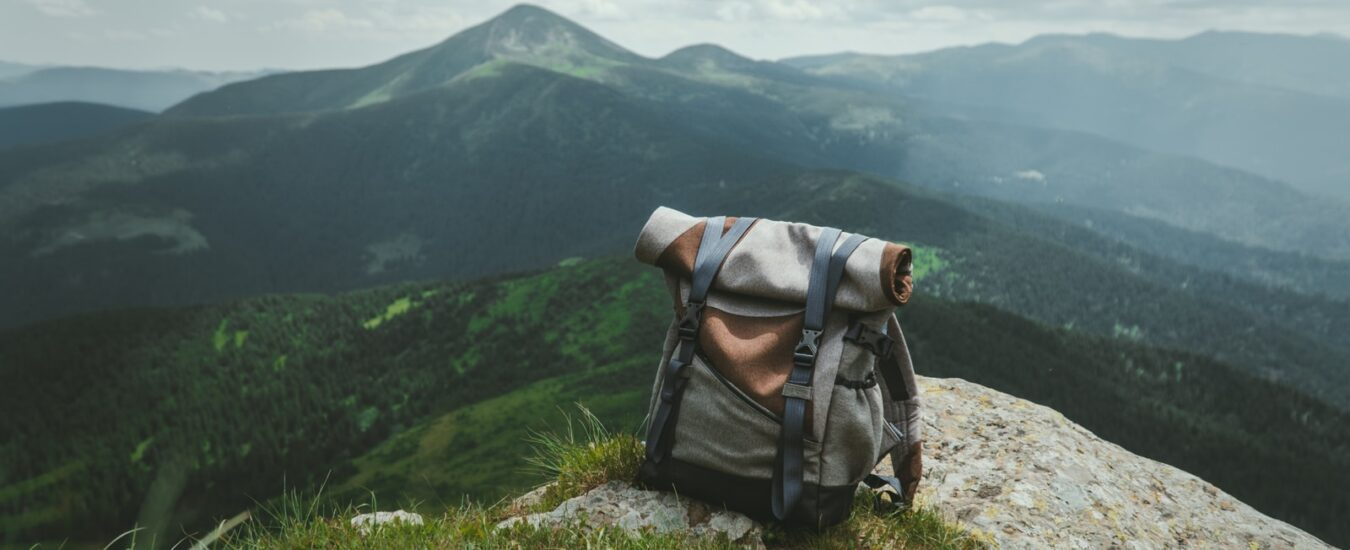 black and gray hiking backpack on green grass field during daytime